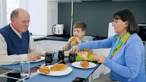 Cover Image for Pensioner, Child Eats Bakery Products with Grandfather and Grandmother in Kitchen
