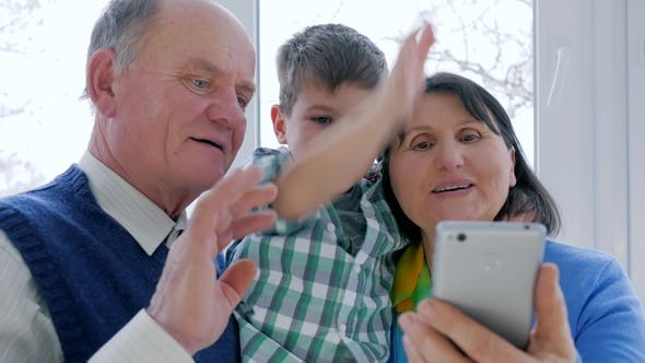 Cover Image for Smiling Grandparents with Cute Kid Talking on Skype in Smartphone in Room