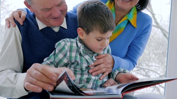 Thumbnail for Pensioner Reading Books, Child with Grandmother and Grandfather Watching Pictures in Journal