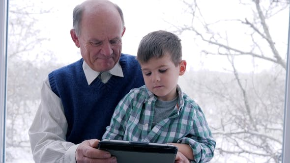 Grandfather and Grandson Play in Video Games at Home