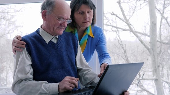 Cover Image for Family Atmosphere, Old People Work with Computer on Internet Indoors