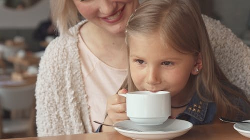 Little Girl Takes a Sip of Tea at the Cafe