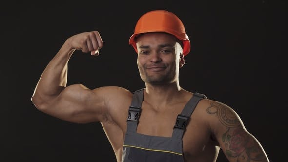 Thumbnail for Muscular Ripped Sexy African Male Builder in Workwear and Hardhat Flexing Muscles