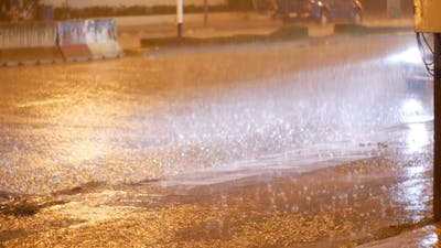 Tropical Rainfall at Night on the Road in Asia. Cars Stand and Ride Under Heavy Rain