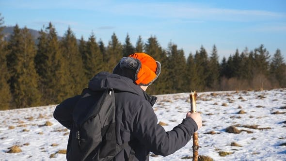 Thumbnail for Side View of Young Hiker with Backpack and Stick in Hand Climbing on Snowy Hill in Field
