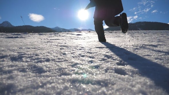 Thumbnail for Unrecognizable Guy Jogging on Snowy Field at Sunny Winter Day Young Man Running on Snowy Meadow