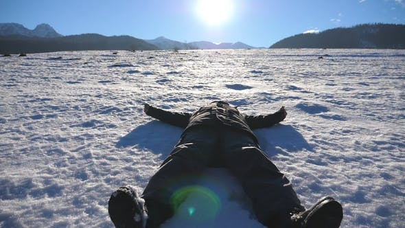 Cover Image for Young Guy Lying on Snow Field and Making Angel on Sunny Day Happy Man Playing and Smiling on Snowy
