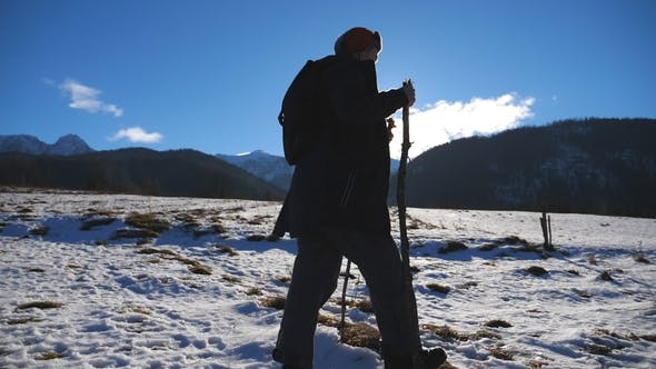 Young Hiker Going Nordic Walking with Sticks on Snowy Trail in Field with Sunlight at Background