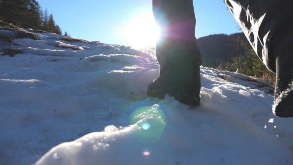 Thumbnail for Rear Back View of Young Hiker Climbing Up on Snowy Slope on Sunny Day. Unrecognizable Man Walking on