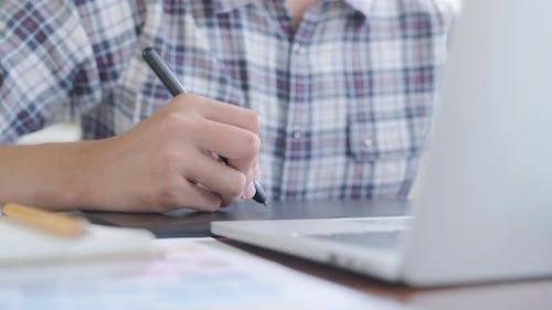 Main rapprochée du graphiste à l'aide d'une tablette graphique.