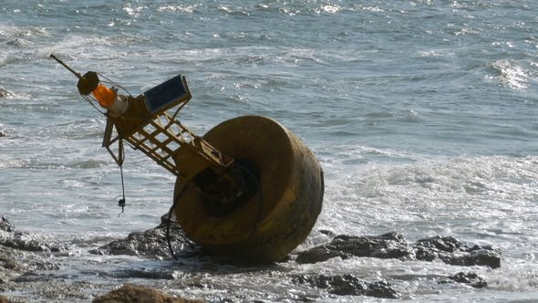 Thumbnail for Old Rusty Yellow Buoy Lies on the Shore of a Rocky Beach