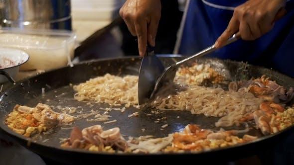 Thumbnail for Asiatische Street Food Meeresfrüchte, Reisnudeln mit Ei Kochen auf einer großen Pfanne