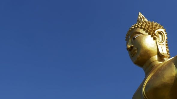 Thumbnail for Statue of a Large Golden Buddha Against a Blue Sky in Thailand Temple