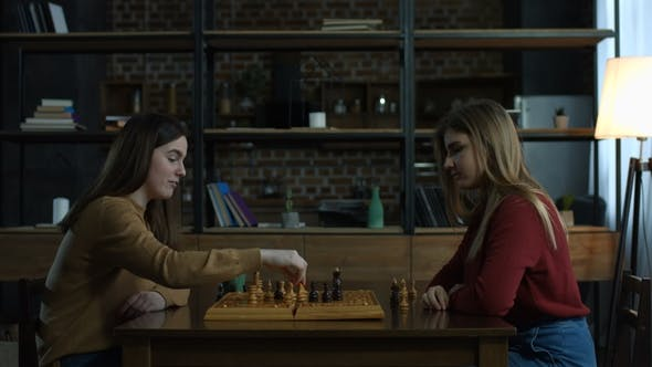 Thumbnail for Two Cheerful Young Women Playing Chess at Home