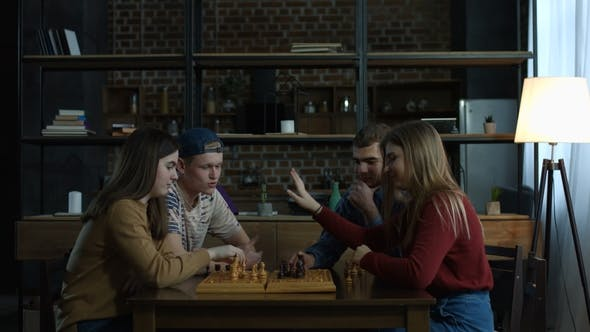 Cover Image for Young Men Teaching Chess Game To Joyful Girlfriends