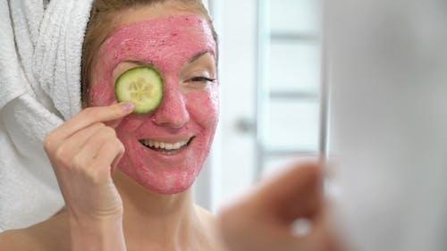 Junge Frau mit einem rosa Gesichtsfeuchtigkeitsspendende Maske spielt mit Gurkenscheiben