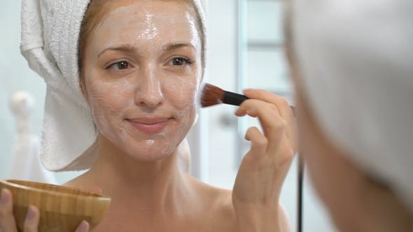 Thumbnail for Young Woman with a White Towel Put on Her Face a Moisturizing Mask