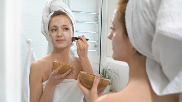 Young Woman with a White Towel Put on Her Face a Moisturizing Mask