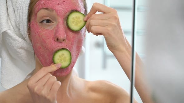 Thumbnail for Young Woman with a Pink Facial Moisturizing Mask Plays with Cucumber Slices
