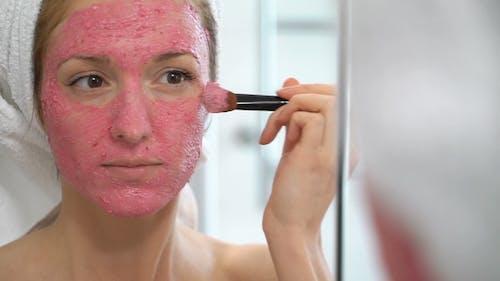Junge Frau mit einem weißen Handtuch setzen Sie auf Ihr Gesicht eine rosa Feuchtigkeitsmaske