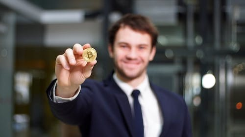 Man Holding in Hand Symbol of Bitcoin Crypto Currency - Electronic Virtual Money for Web Banking.