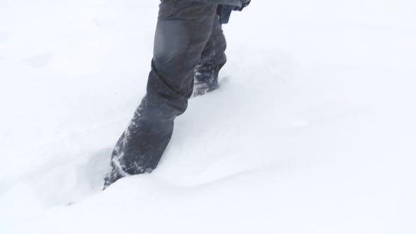 Walking Feet in Boots on a Winter Landscape