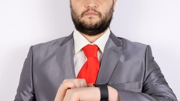 Thumbnail for Bärtiger Geschäftsmann überprüft seine Smartwatch