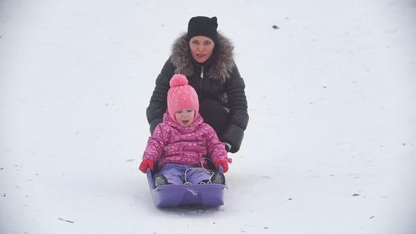 Thumbnail for Mom Rolling Her Little Daughter on a Sled in a Winter Park