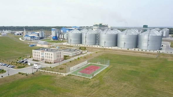 Thumbnail for Aerial View of Grain Elevators Surrounded By Green Fields