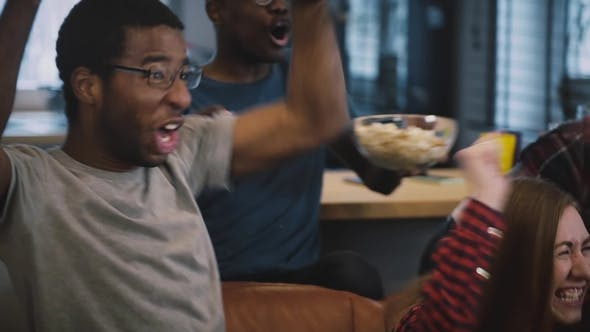 Thumbnail for African American Guy Watching Sports with Friends, Popcorn and Drinks. . Football Fan. Emotional