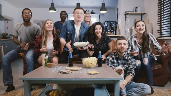 Thumbnail for Diverse Group of Friends Watching Sports on TV Football Supporters Celebrate Success with Popcorn