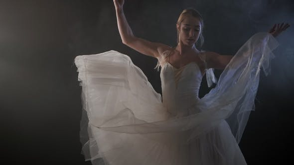 Thumbnail for Mid Shot of a Beautiful Young Ballerina Spinning Gracefully in the Spotlight. She Dressed in White