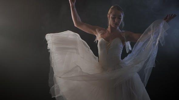 Thumbnail for Mittlerer Schuss einer schönen jungen Ballerina, die sich anmutig im Rampenlicht dreht. Sie gekleidet in weiß