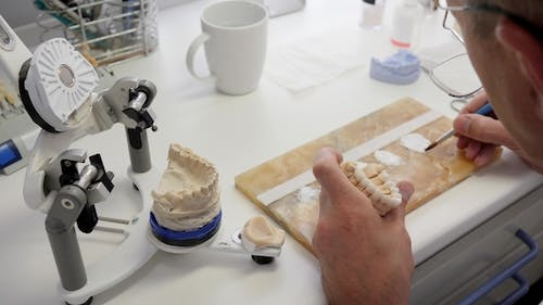 Making Dental Prosthesis for Patients, Specialist Man in Glasses Smears Enamel on Artificial Teeth