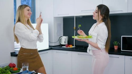 Evening Meal, Women Make Photo on Mobile with Plate in Arms at Kitchen Interior
