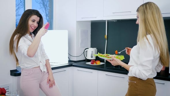 Thumbnail for Healthy Eating, Beautiful Girlfriends with Salad in Arms Make Photo on Smartphone at Kitchen