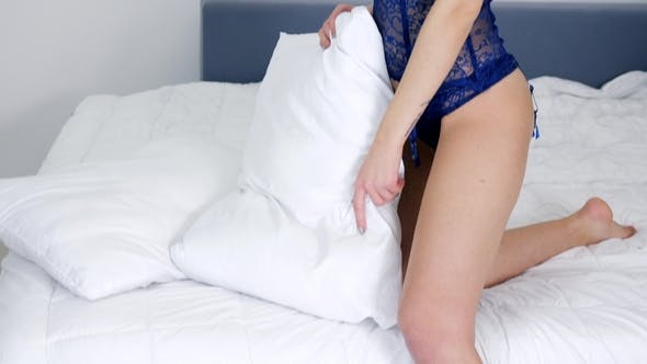 Cover Image for Happy Woman with Red Lips in Lace Underwear with Pillow in Hands at Home