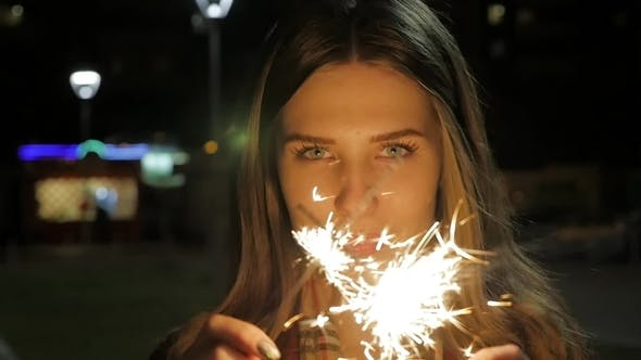 Young Smiling Girl Holding Sparkler in Her Hand. Portrait of Girl Holding Sparkles in