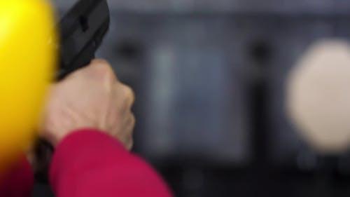 Back View of Man Shoots a Gun at Shooting Range . Man Fires Hand Gun at Indoor Shooting Range. .  o