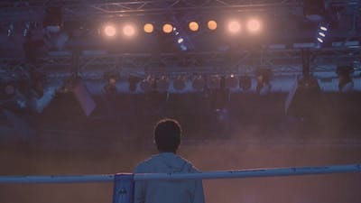 Back View of Working Gaffer or Lighting Technician and Spotlights Background. Lighting Technician