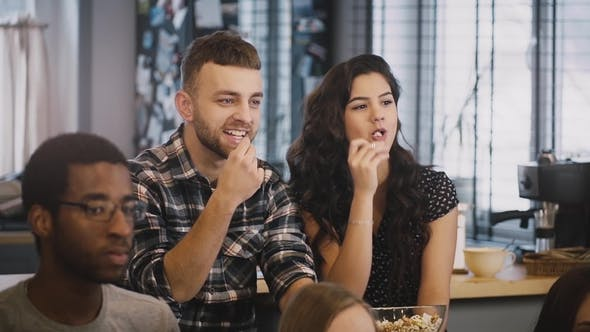 Cover Image for Cute Couple Watch Funny Film on TV with Friends. Caucasian Guy and Girl Sit Together, Eat Popcorn