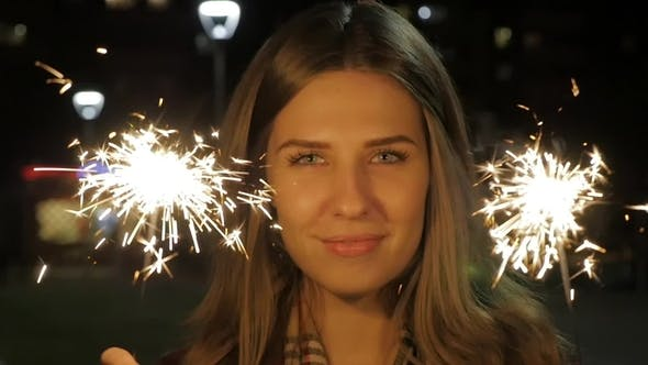Thumbnail for Smiling Teenage Girl on the Street at Night with Sparklers. Young Woman Celebrating an Event the New