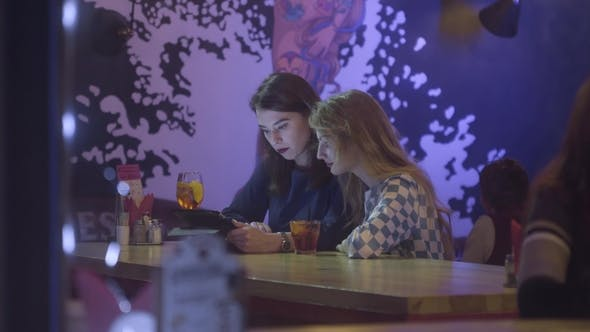 Thumbnail for Two Female Friends with Tablet Computer Sitting in Cafe, Outdoors. Pretty Girlfriends with