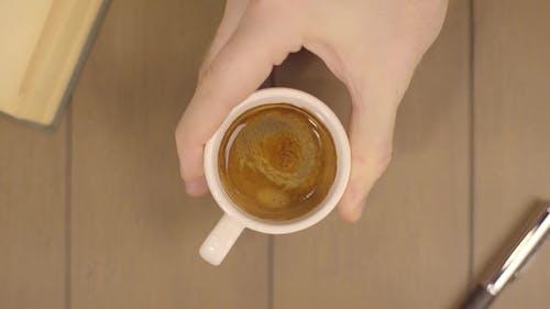 Human Hand hält Kaffeetasse Morning Drinks. Männlich bewegt eine Tasse Kaffee. Tasse Kaffee mit fließenden
