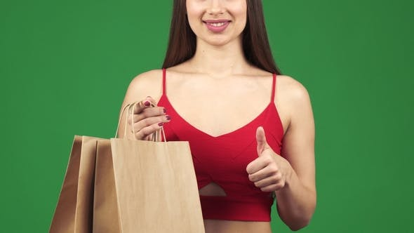 Thumbnail for Woman Smiling Holding Shopping Bags Showing Thumbs Up
