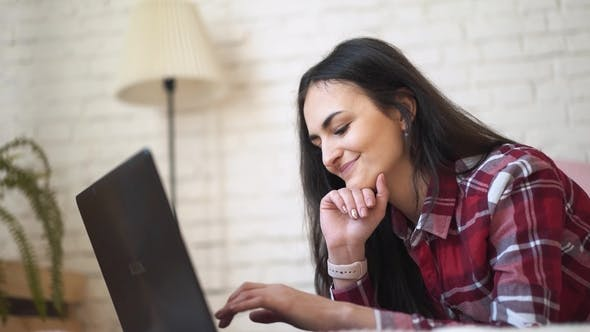 Thumbnail for Young Woman Working at Home Behind Laptop. Dressed in a Plaid Shirt, Against a Brick Wall Background