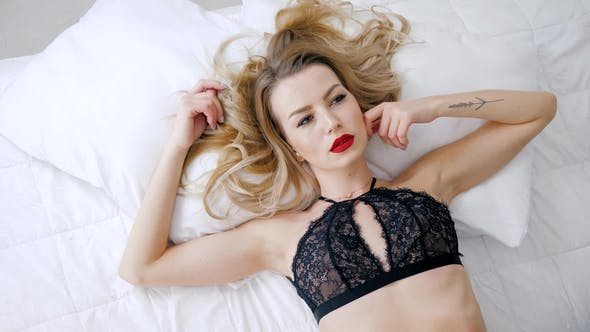 Cover Image for Erotic Portrait of Young Woman with Red Lips in Black Lace Underwear Lies on White Bed
