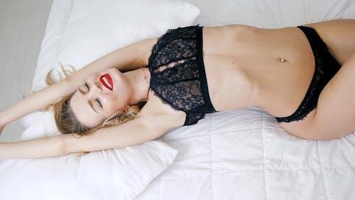 Happy Morning, sexy Mädchen mit schlanken Körper in erotische Dessous liegt auf weiß Bett