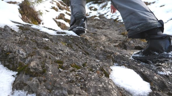 Thumbnail for Feet of guy climbing up on trail of hill at morning. Young male tourist walking on snowy mountain