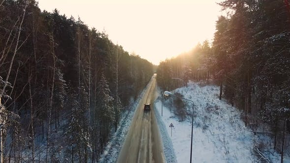 Thumbnail for Car Rides By Road in Snow-covered Forest. Footage. Rays of the Morning Sun. Aerial View. Aerial View